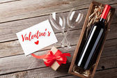 Photo Valentines day greeting card. Red wine and gift box on wooden table. Top view with copy space