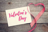 Blank valentines greeting card and red heart shaped ribbon on wooden background