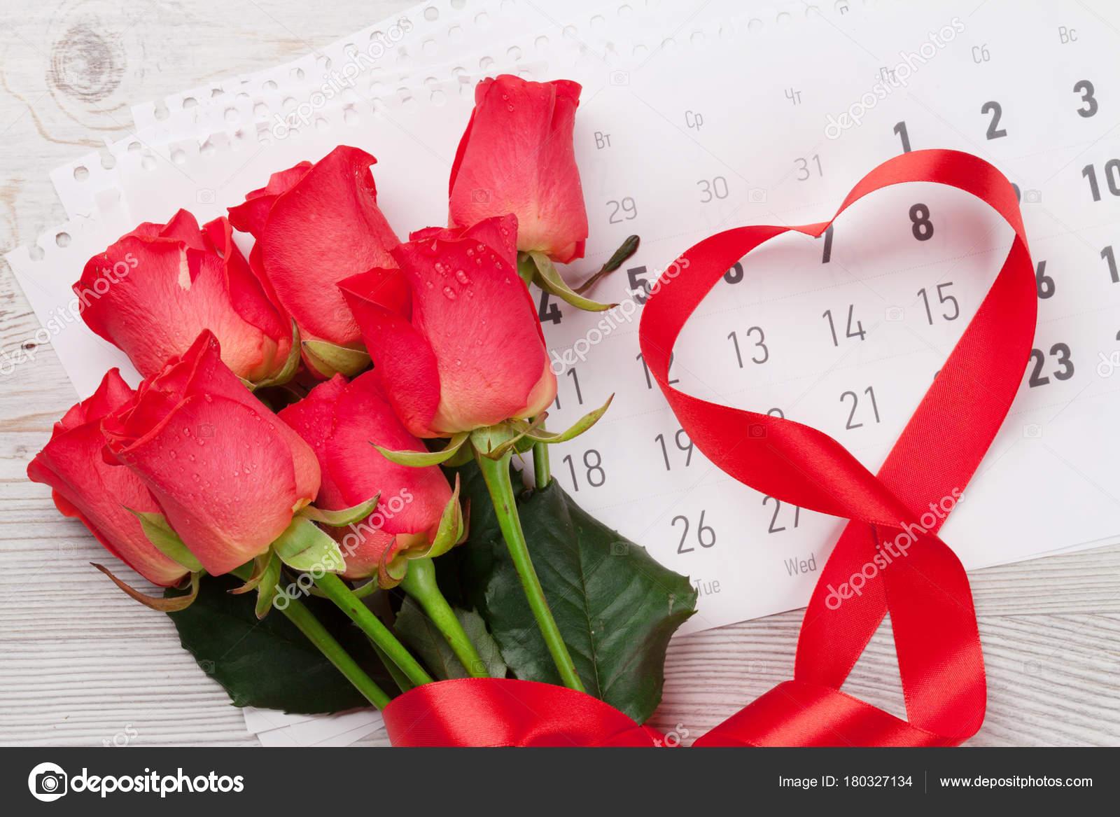 1289a7bd71ec Día de San Valentín tarjeta de felicitación con rosas rojas y corazón en  forma de cinta sobre el calendario de febrero sobre fondo de madera.
