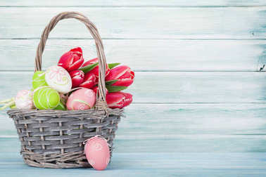 Red tulips bouquet in basket and easter eggs in front of wooden wall.  Easter greeting card.