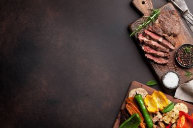 Grilled vegetables and beef steak on cutting board on wooden table. Top view with copy space