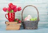 Červený Tulipán květy kytice a velikonoční vejce před dřevěnou stěnou. Velikonoční blahopřání