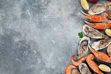 Seafood. Octopus, lobster, clams cooking. Top view on stone table with space for your text