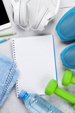 Fitness concept background with sneakers, dumbbells, water bottle, smartphone and headphones. Top view with notepad for your text