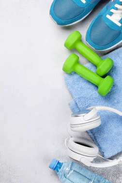 Fitness concept background with sneakers, dumbbells, water bottle and headphones. Top view with space for your text