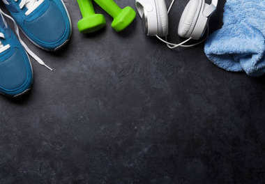 Fitness concept background with sneakers, dumbbells, towel and headphones. Top view with space for your text