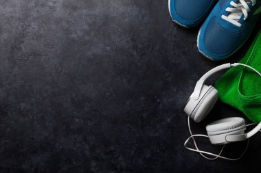Fitness concept background with sneakers, towel and headphones. Top view with space for your text