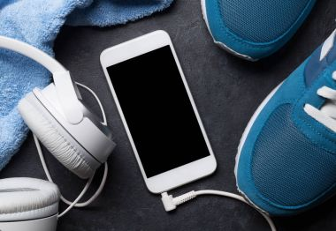 Fitness concept with sneakers, smartphone, towel and headphones. Top view with copy space