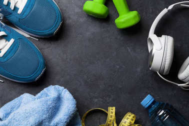 Fitness concept background with sneakers, headphones, dumbbells, water bottle and tape measure. Top view with space for your text