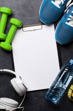 Fitness concept background with sneakers, headphones, dumbbells, water bottle. Top view with space for your text