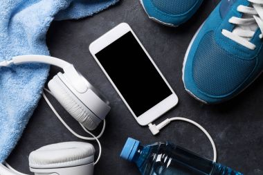 Fitness concept background with sneakers, headphones, smartphone, water bottle and towel. Top view with copy space