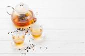 Bylinkový a Ovocný čaj, čajník a šálky na dřevěném stole. S prostorem pro kopírování