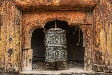 Buddhist prayer mani wall with prayer wheels in nepalese village on the Annapurna circuit trekking route, Nepal stock vector