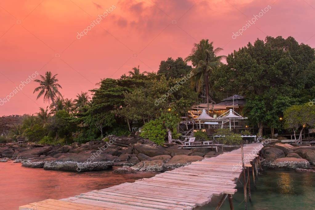 Wooden pier to a tropical island resort on Koh Kood island during sunset, Thailand.