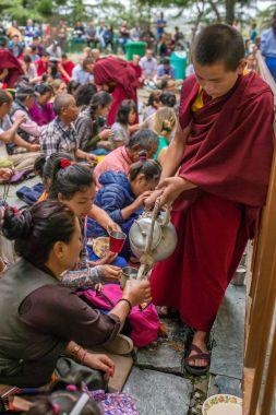 Dharamsala, India - June 7, 2017: Buddhist monk serve tibetan tea to the listeners during his Holiness the 14 Dalai Lama Tenzin Gyatso teachings in his residence in Dharamsala, India.