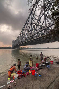 Kolkata, India - April 6, 2017: Low angle view of Howrah bridge with people washing clothes in Hooghly river