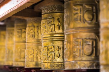 Tibetan buddhist praying wheels in Ladakh, India. Traditionally, the mantra Om Mani Padme Hum is written in Sanskrit on the outside of the wheel stock vector
