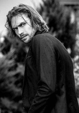 Black-white outdoor portrait of elegant long hair handsome man.
