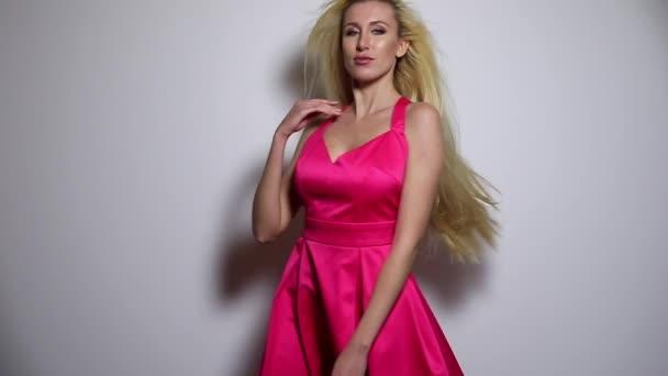 Krásná sexy žena v růžových šatech představují proti studio pozadí. Slow Motion záběry.