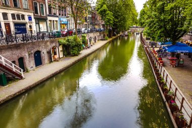 The most famous canals and embankments of Utrecht city during sunset. General view of the cityscape and traditional Netherlands architecture.