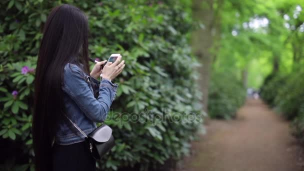 Long-haired beautiful girl in a blooming summer park with phone. Slow Motion Footage.