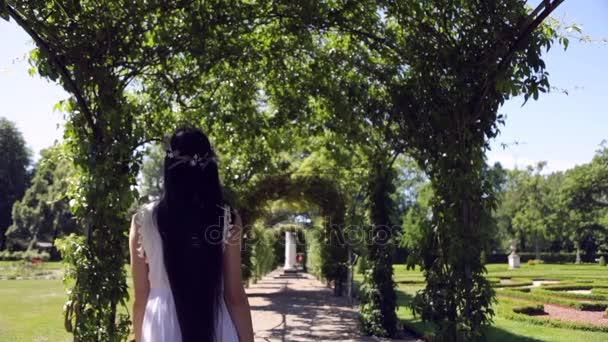 Lungo-haired ragazza bella in corona di fiori ad una fioritura estate parco. Slow Motion Footage