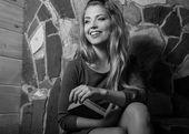 Mladá usmívající se žena krásy s knihami proti interiér domu