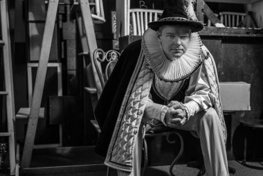 Actor dressed historical costume in interior of old theater. Black-white portrait.