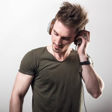 Handsome friendly sporty man in green t-shirt listening music against gray studio background.