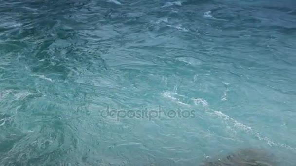 Na pozadí modré vody a vln. Slow Motion záběry