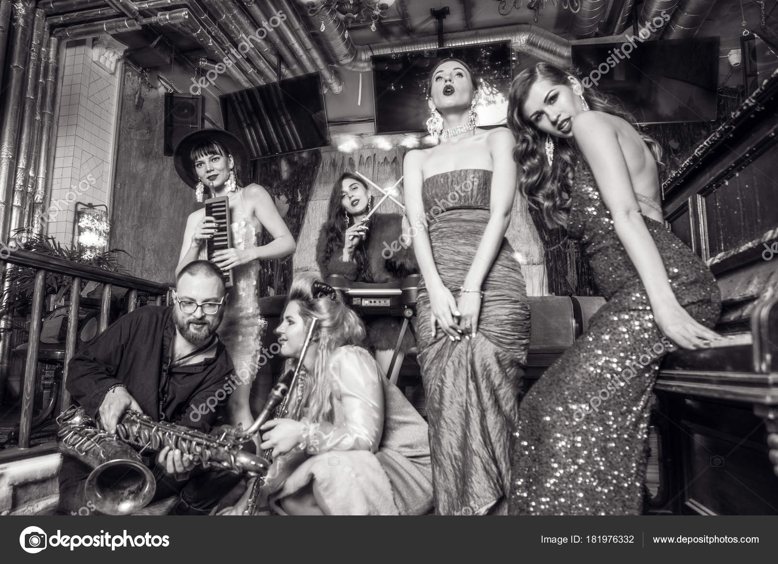 7b8dcf82c52 Grupo de jovens elegantes vestidos estilo clássico no interior do clube de  luxo. Foto preto