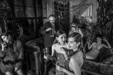 Group of young stylish people dressed classical style in interior of luxury club. Black-white photo.