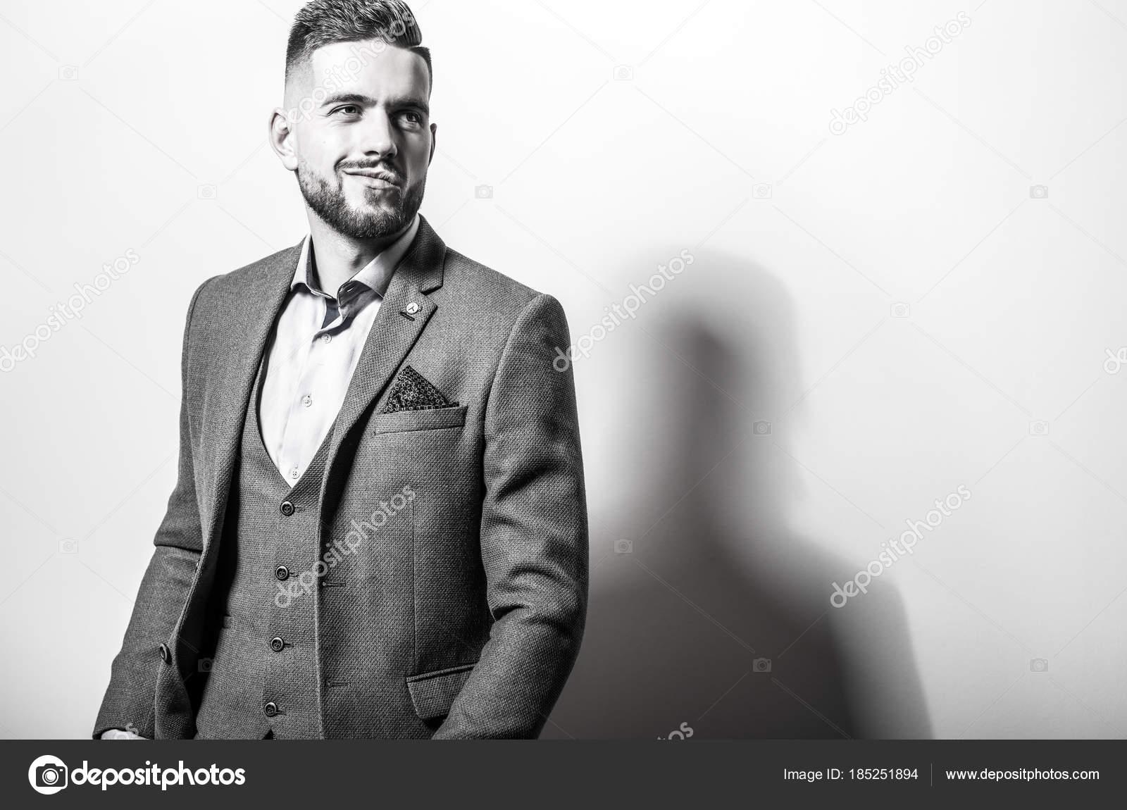 Handsome Young Elegant Man In Grey Jacket Pose Against Studio
