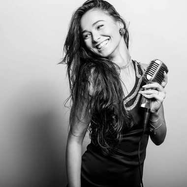 Young sensual woman in black dress with microphone. Black-white portrait.