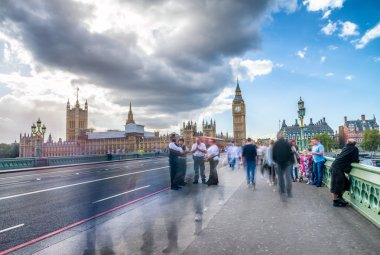Blurred image of tourists walking along river Thames in London,