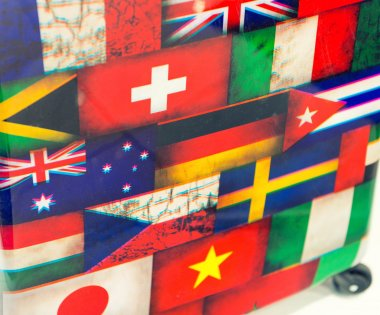 International flags printed on a luggage. Tourism concept