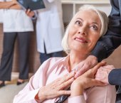 Photo Mature woman on wheel chair giving hand to husband. Healthcare a