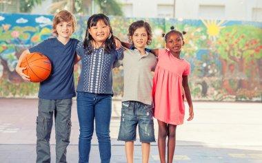 Happy mixed race primary classroom embracing in schoolyard. Inte