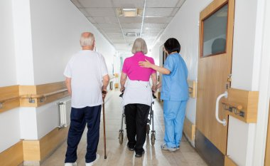 Rehab facility with two elder patients helped by nurse, back vie