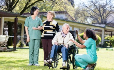 Afroamerican and asian nurses joking with elder people in hospit
