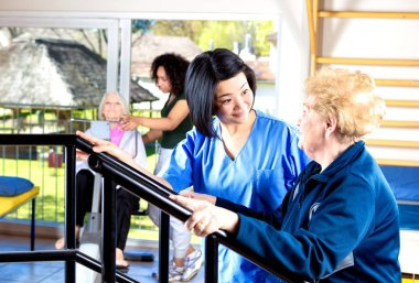 Old people working out in hospital rehab gym helped by nurse