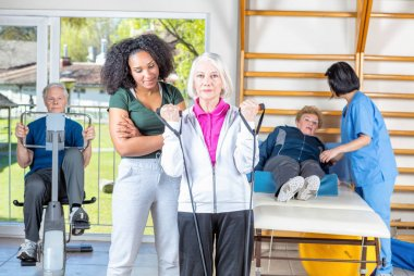 Rehab clinic gym. Multi racial nurses helping elder patients