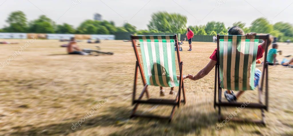 Father and daughter laying on beach chairs in a city park, back
