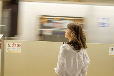 Asian woman awaiting subway train in the station