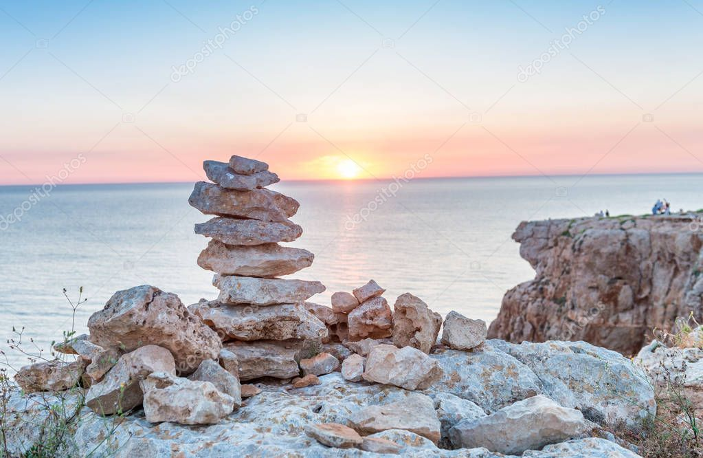 Stacked stones over the sea at sunset