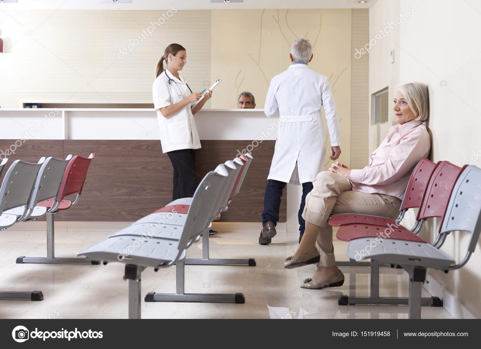 In Sala D Attesa.Medici E Pazienti Discutendo In Sala D Attesa Ospedale Foto Stock