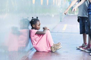 Smiling african schoolgirl alone in a school corner. Bullying co