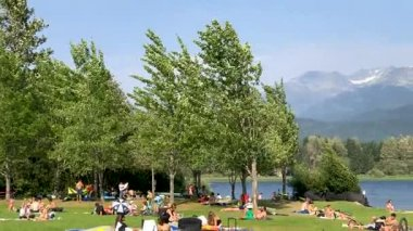 people relaxing near lake surrounded with evergreen forest and mountains, video