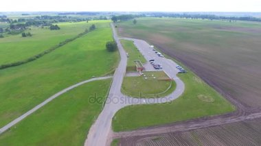 Overhead aerial panoramic view of meadows in summer season and parking lot. Video