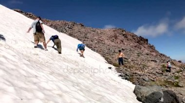 people climbing snowy mountains on a sunny day